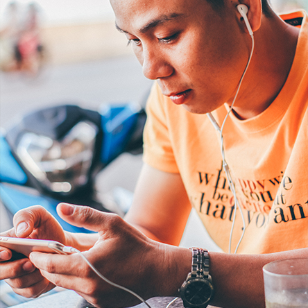 A man playing a mobile game in a brightly coloured t-shirt